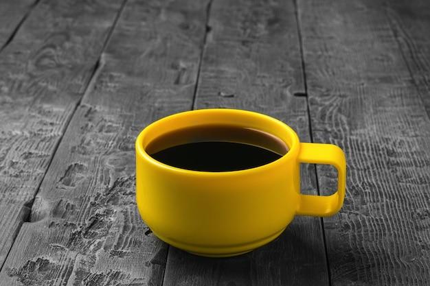 Une tasse jaune avec du café noir sur une table en bois. une boisson chaude revigorante.