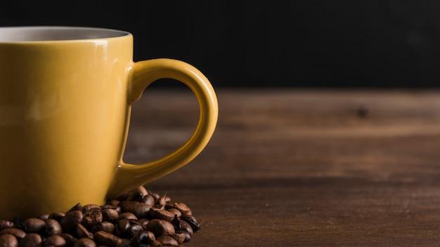 Tasse jaune avec grains de café