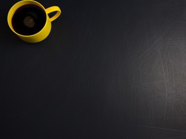 Tasse jaune tasse de café noir à plat sur fond noir rugueux rayé style minimal