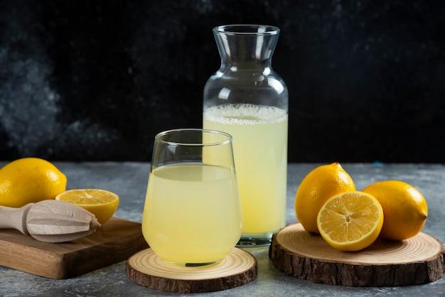 Une tasse de jus de citron sur planche de bois.