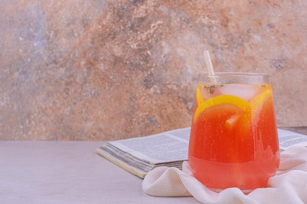 Une tasse de jus avec des tranches de fruits dedans