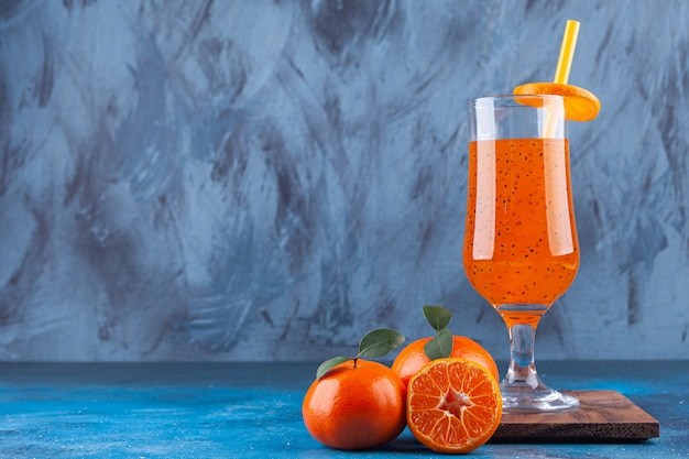 Une tasse de jus en verre avec de la paille et des mandarines entières et tranchées.