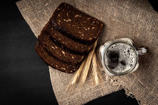 Tasse de kvas avec du pain de seigle sur fond noir.