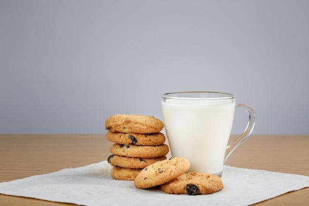 Tasse de lait et biscuits aux raisins secs sur une table en bois