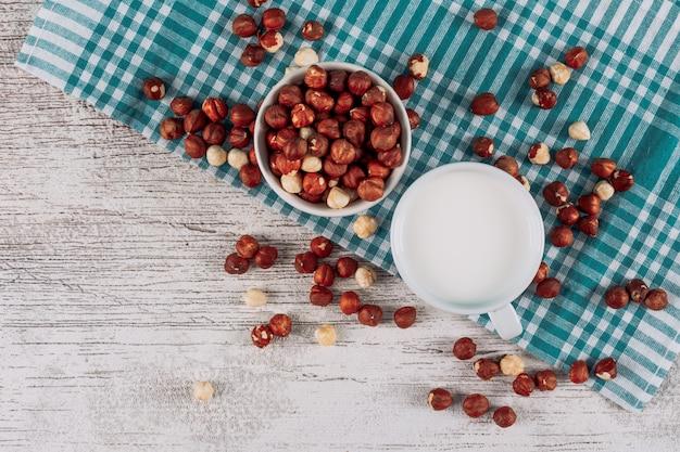Une tasse de lait avec un bol de noisettes sur fond de tissu blanc en bois et bleu, vue de dessus.