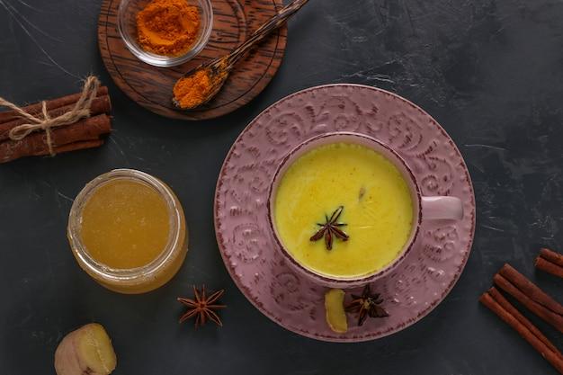 Tasse de lait latte au curcuma doré ayurvédique avec poudre de curcuma, cannelle, gingembre et étoile d'anis sur fond sombre, vue de dessus