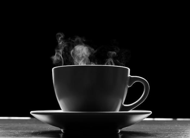 Tasse avec liquide chaud sur fond noir