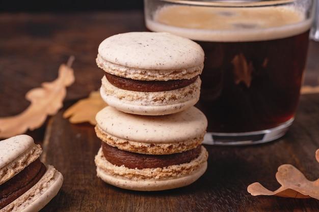 Tasse de macarons au café et au chocolat sur fond en bois. composition d'automne confortable - image