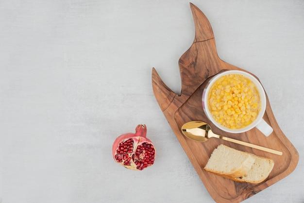 Tasse de maïs sucré avec tranche de pain sur planche de bois.