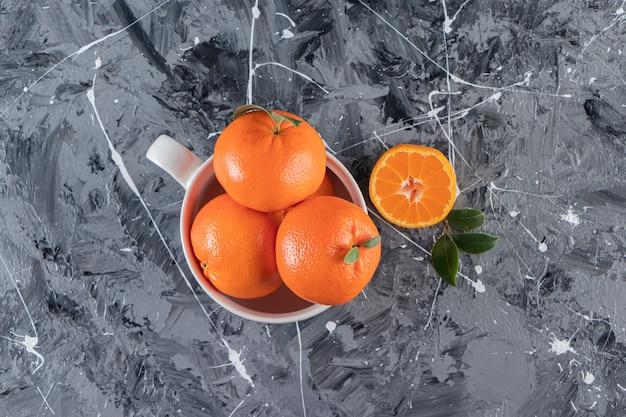 Une tasse de mandarine mûre, sur la table mixte.
