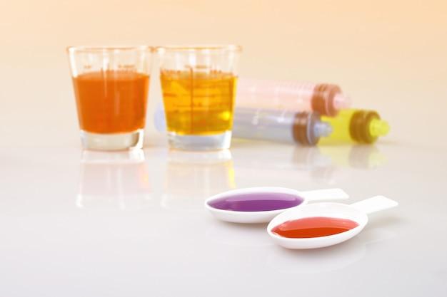 Tasse de médicament, seringue pour administration orale et cuillère à thé contenant un médicament à base de sirop pour administration orale.