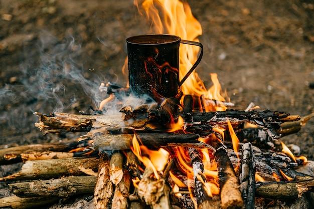 La tasse en métal se réchauffe sur un feu de joie