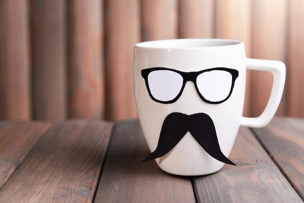 Tasse avec moustache sur table en bois