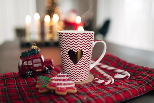 Tasse de noël blanc rouge, biscuits, bonbons, sucette et voiture. photo de haute qualité