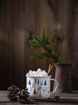 Tasse de noël de cacao et de guimauve à la cannelle sur une vieille table en bois marron avec des cônes et du sapin. ambiance du nouvel an. vue de face et espace de copie