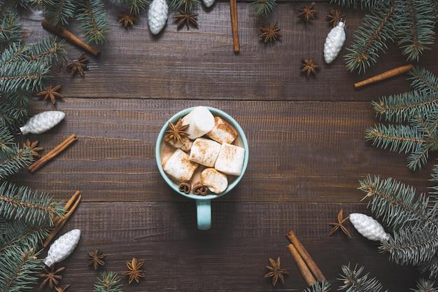 Tasse de noël de café chaud à la guimauve sur une planche de bois.