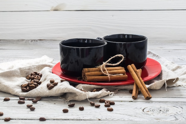 Tasse noire, mur en bois, boisson, matin de noël, grains de café, bâtons de cannelle