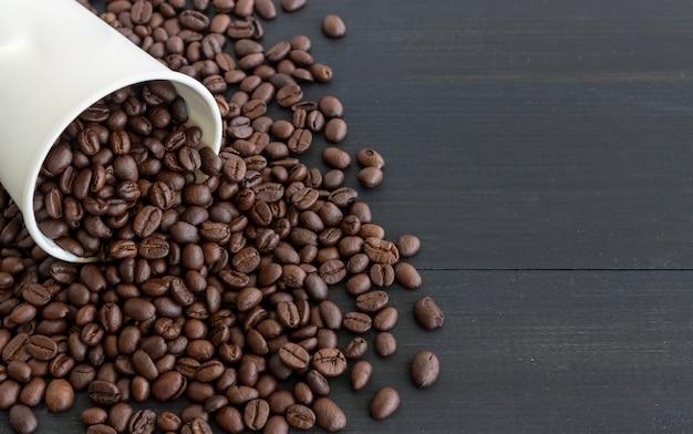 Tasse de papier blanc et grains de café sur vieux bois
