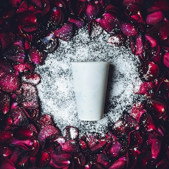 La tasse de papier blanc se trouve dans la poudre blanche dans le cercle des pétales de rose rouge