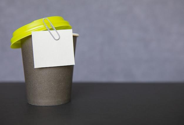 Tasse en papier de café et autocollant de trombone sur fond flou gris