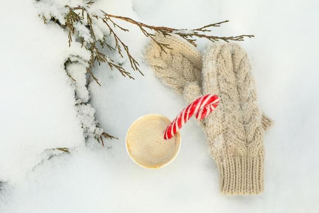 Tasse en papier avec café et cannes à sucre et mitaines en plein air en hiver
