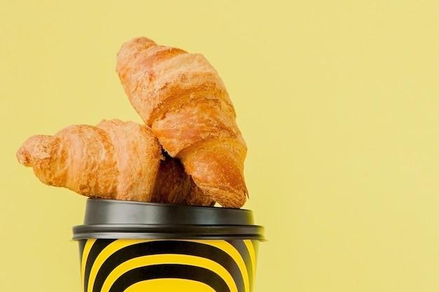 Tasse en papier de café et croissants sur fond jaune.