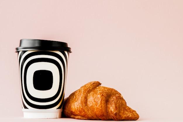 Tasse en papier de café et de croissants sur un mur rose, espace copie.