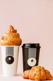 Tasse en papier de café et croissants sur une rose