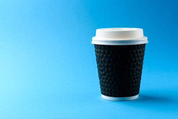 Tasse de papier de café sur fond bleu.
