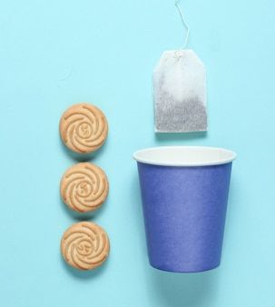 Tasse de papier jetable vide pour le thé, sachet de thé, biscuits sur une surface pastel bleue, vue de dessus, minimalisme