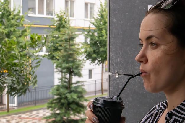 Une tasse en papier noir avec un couvercle et une paille dans les mains d'une jeune femme souriante heureuse à l'extérieur en été par temps ensoleillé sur le fond des maisons, dans un café ou un restaurant. café à emporter.