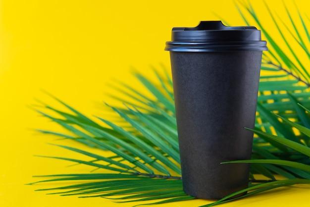 Tasse en papier pour le café avec une branche de palmier sur fond jaune