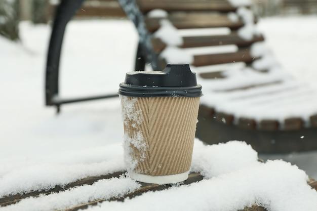 Tasse de papier vierge sur un banc en plein air en hiver