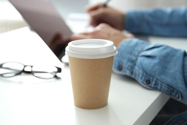 Tasse de papier vierge contre un jeune homme travaillant sur un ordinateur portable.