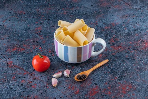 Une tasse de pâtes cannelloni crues avec des légumes et des grains de poivre sur une surface sombre.