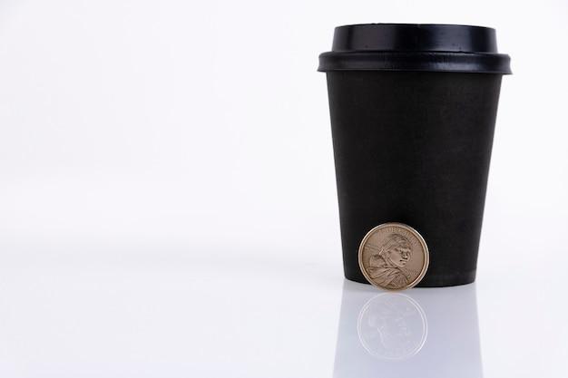 Tasse en plastique fermée noire pour le café ou le thé avec une pièce d'un dollar, sur fond blanc. espace de copie.