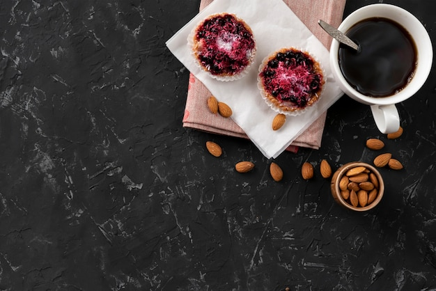 Tasse plate avec café chaud, gâteau sucré sur une table noire, petits déjeuners cuisinés à la maison