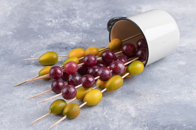 Une tasse pleine de baguettes avec des raisins rouges mûrs et des kumquats sur un marbre.