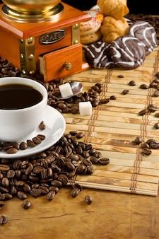 Tasse pleine de café, haricots, pot et moulin sur motif en bois