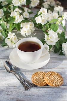 Tasse en porcelaine blanche avec du thé et deux biscuits à l'avoine avec des graines de sésame sur une table en bois dans le contexte de la floraison du jasmin.