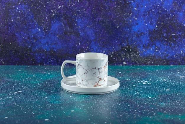Tasse en porcelaine blanche sur table bleue.