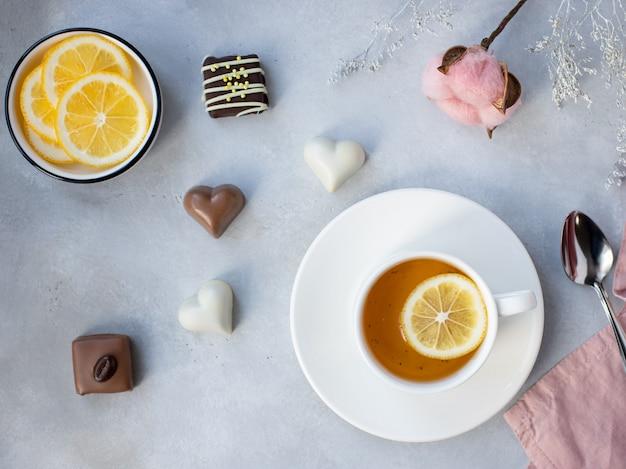 Tasse en porcelaine de thé vert au citron et divers bonbons sur une surface grise avec des fleurs. printemps. image horizontale, vue de dessus, mise à plat. concept de la saint-valentin