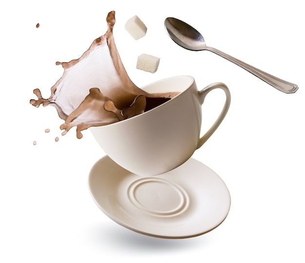 Tasse qui tombe avec des éclaboussures de café, des cubes de sucre raffiné et une cuillère à café sur blanc