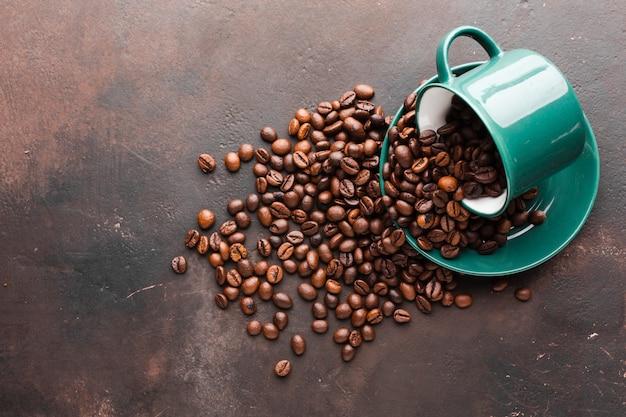 Tasse renversée avec grains de café
