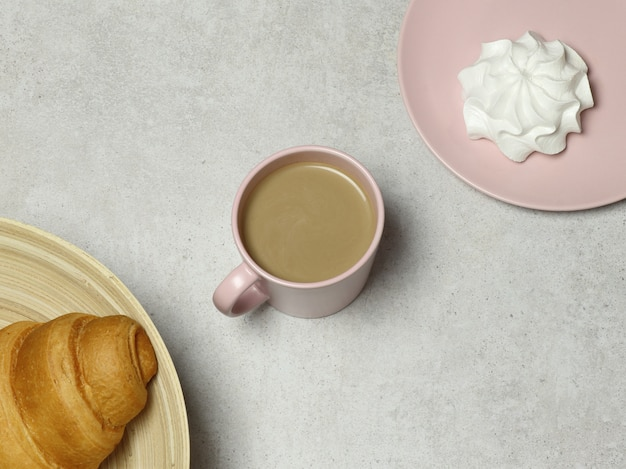 Tasse rose de cappuccino à la guimauve et croissant sur fond de granit