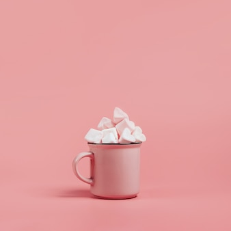 Tasse rose sur une surface rose remplie de guimauves en forme de coeurs.
