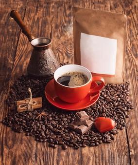 Une tasse rouge de café, coeur, haricots, cafetière turque et sac pochette en papier craft sur motif en bois