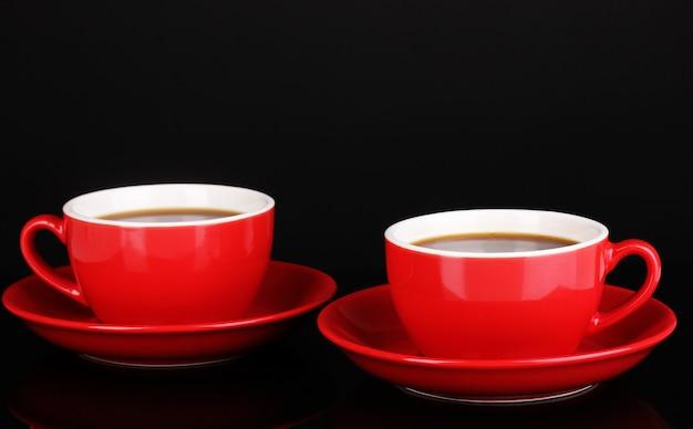 Une tasse rouge de café fort sur fond noir