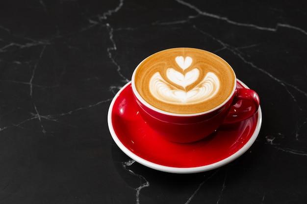 Tasse rouge de café latte chaud avec une belle texture d'art latte en mousse de lait isolée sur fond de marbre foncé. vue aérienne, copiez l'espace. publicité pour le menu du café. carte du café.