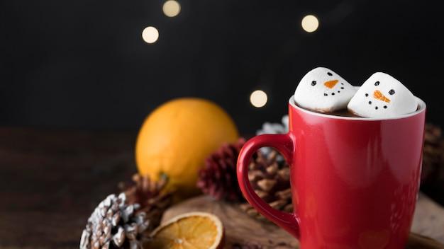 Tasse rouge de chocolat chaud avec des guimauves avec espace copie